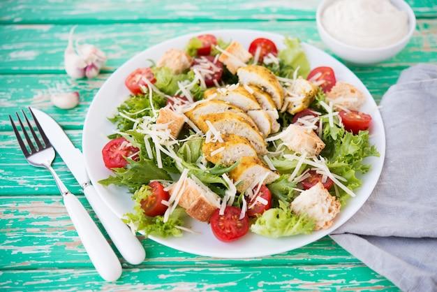 Салат цезарь с куриной грудкой на деревенском фоне, помидоры, пармезан, зеленый салат и гренки, выборочный фокус