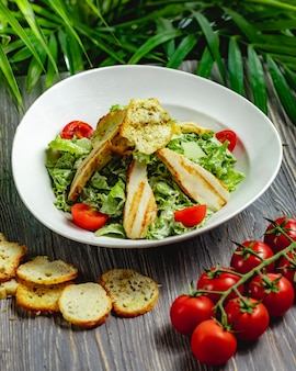 Caesar salad with chicken and cherry tomatoes in a white plate on a wooden table