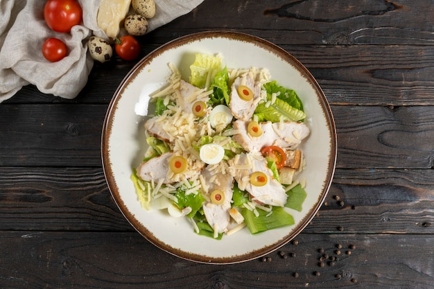 鶏の切り身、レタス、オリーブ、チーズ、チェリートマト、ウズラの卵、カリカリのクルトンのシーザーサラダ