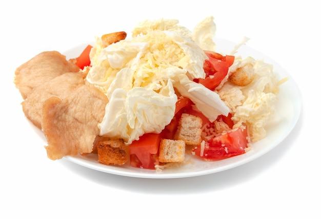 치킨 필레, 북경 양배추, 파마산 치즈, 크래커, 토마토를 곁들인 시저 샐러드. 하얀 접시에. 외딴. 흰색 배경에