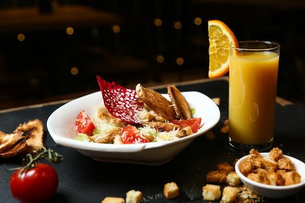 Caesar salad con pollo e un bicchiere di succo d'arancia