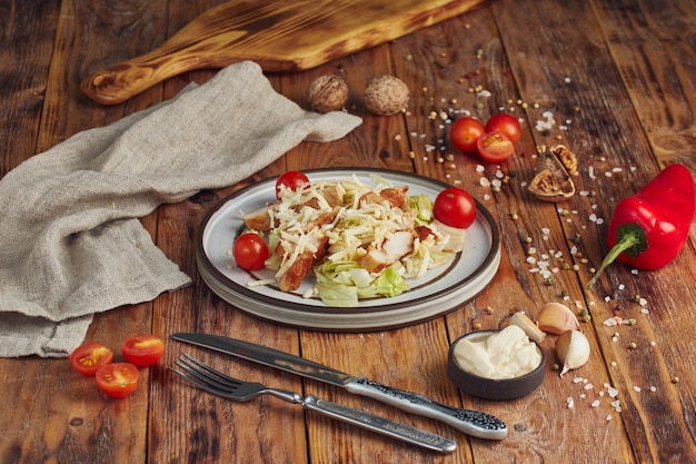 Салат цезарь с курицей в белой тарелке на деревянном столе