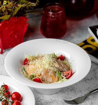 Caesar salad with chicken lettuce tomato and parmesan grates