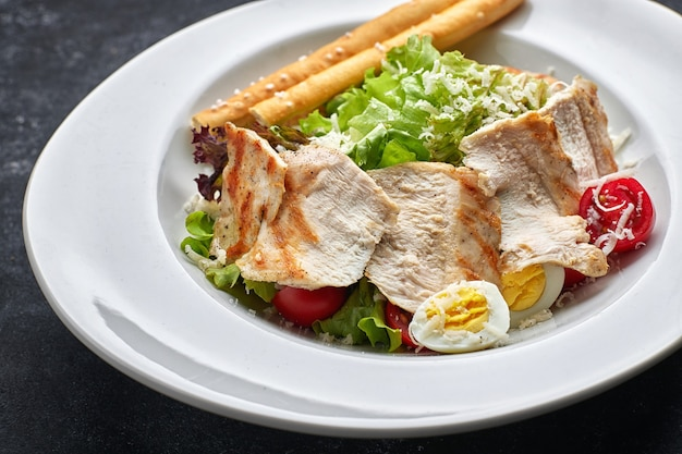 흰 접시에 닭고기, 양상추, 토마토, 치즈, 계란 시저 샐러드
