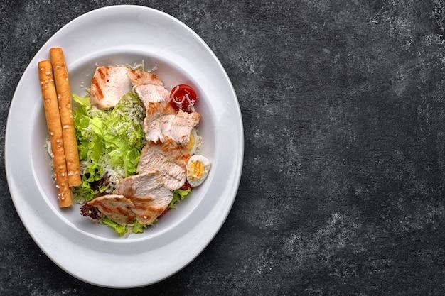 Салат цезарь с куриным мясом, листьями салата, помидорами, сыром и яйцами, на белой тарелке