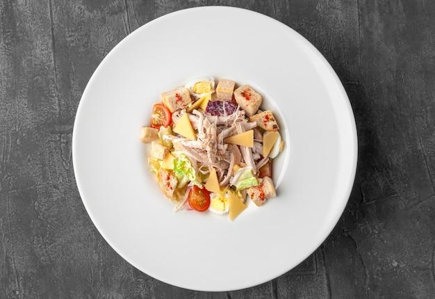 鶏肉のシーザーサラダ。大きな白いお皿に。上からの眺め。灰色のコンクリートの背景。