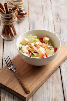Салат цезарь с курицей на деревянной доске
