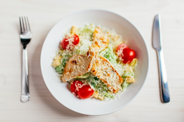 Caesar salad with chicken on white wooden table with fork and knife.