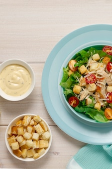 Caesar salad with chiken  on a white wooden table top view no people