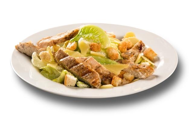 Салат цезарь с гренками и жареной курицей на белой поверхности.