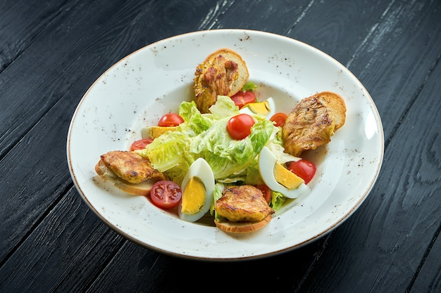 Caesar salad with croutons, parmesan, bacon, chicken, egg in black plate on wooden background.