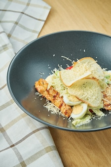 Caesar salad with croutons, parmesan, chicken, egg in a black stylish bowl. restaurant serving. selective focus, wooden table