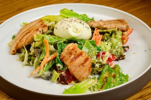 Салат цезарь с гренками, перепелиными яйцами, помидорами черри и жареной курицей на деревянном столе. вкусный салат с курицей, орехами, яйцом и овощами.
