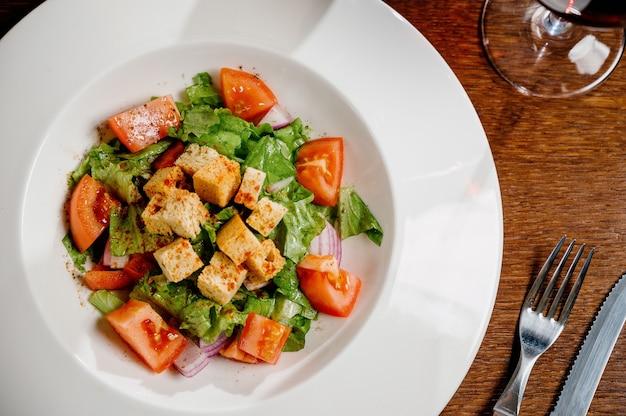 Салат цезарь с гренками, перепелиными яйцами, помидорами черри и курицей гриль на деревянном столе