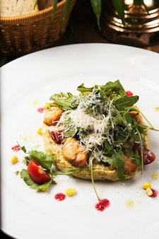 Caesar salad with fresh vegetable and chicken. salad in white plate on wood table, delicious salad