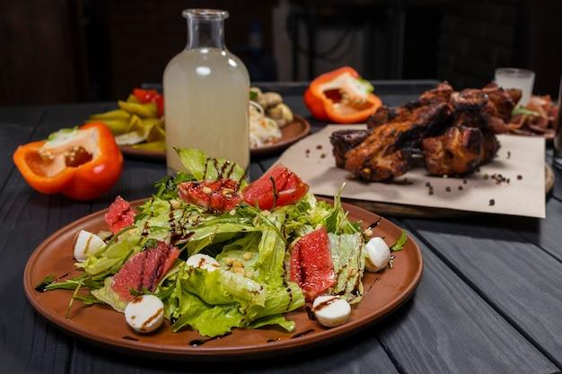 Салат цезарь с грейпфрутом со свиными ребрышками на гриле маринованные овощи и самогон