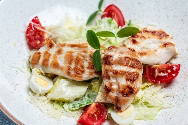 Caesar salad with grilled chicken breast fillet and parmesan cheese. food recipe background. close up.