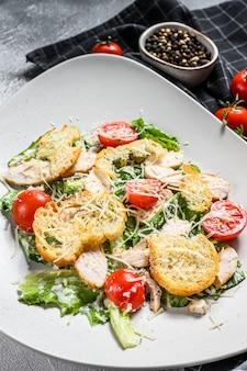 Салат цезарь с курицей гриль, гренками, перепелиными яйцами и помидорами черри. вид сверху