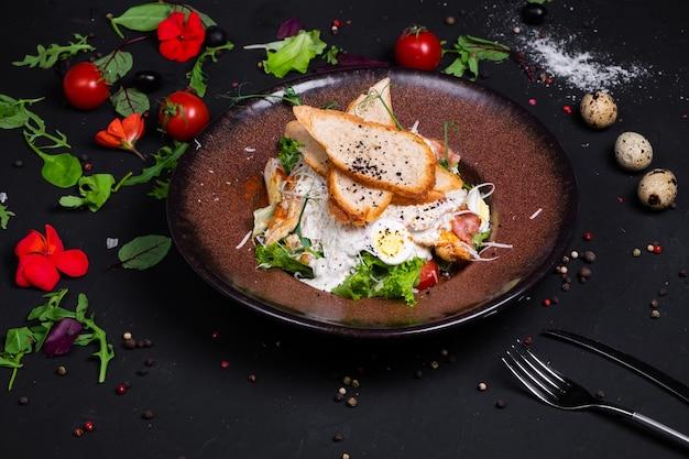 グリルチキンフィレとベーコンのスライス、トマトとシーザーソースのシーザーサラダ。