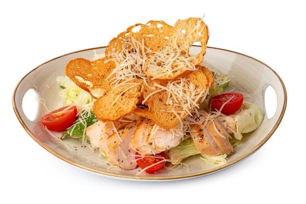 Caesar salad with grilled chicken on white wooden background