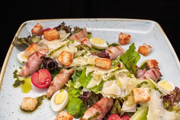 Салат цезарь с зеленью, куриным беконом, яйцами и помидорами на квадратной светлой тарелке на темном фоне