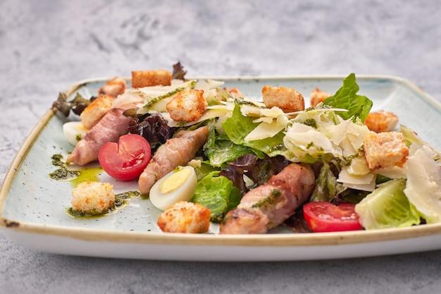 Салат цезарь с зеленью курица, бекон, яйца и помидоры на квадратной светлой тарелке