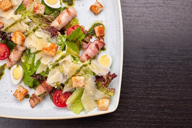 Caesar salad with herbs chicken bacon eggs and tomatoes on a square light plate on a dark background