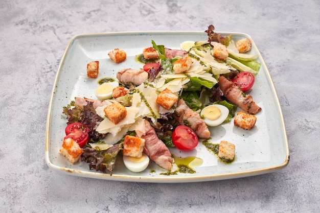 Caesar salad with herbs chicken bacon eggs and tomatoes on a square light plate