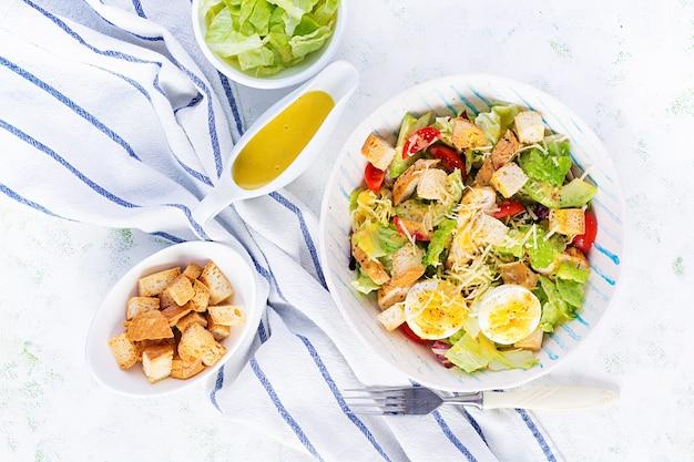 Салат цезарь с листьями салата, курицей, авокадо, помидорами черри и гренками на светлом столе