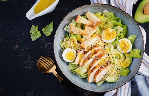 Caesar salad with lettuce, chicken, avocado and croutons on dark table