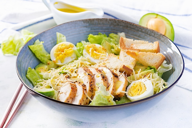 Caesar salad with lettuce, chicken, avocado and croutons on light table