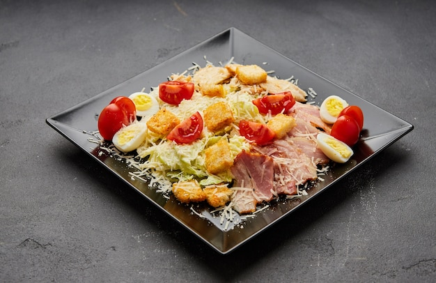 Caesar salad with lettuce, chicken, bacon and croutons on dark background