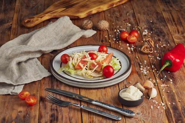 Салат цезарь с лососем в белой тарелке на деревянном столе. вкусный салат из морепродуктов.