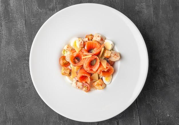 サーモンのシーザーサラダ。大きな白いお皿に。上からの眺め。灰色のコンクリートの背景。