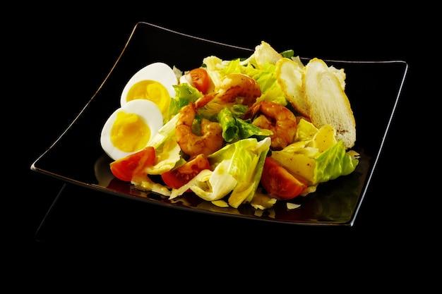 Салат цезарь с креветками, яйцом, помидорами черри, гренками и соусом цезарь.