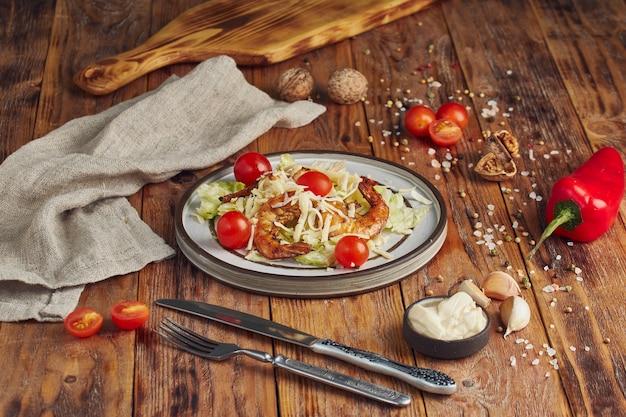 Салат цезарь с креветками в белой тарелке на деревянном столе