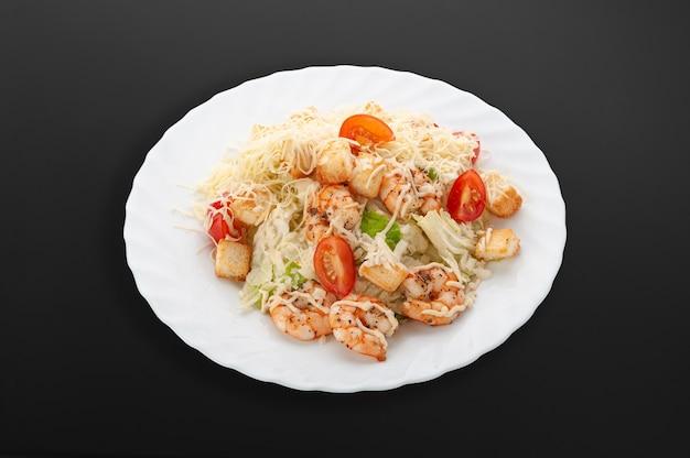 하얀 접시에 새우와 함께 시저 샐러드입니다. 새우, 체리 토마토, 샐러드 믹스, 크루통, 파마산 치즈, 소스. 어두운 배경입니다. 외딴. 확대.