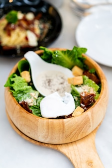 Caesar salad on wood bowl