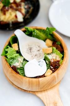 Caesar salad on wood bowl