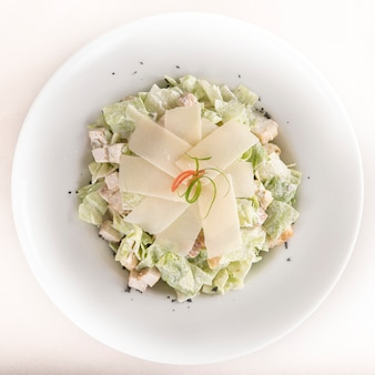 Caeser salad with chicken fillet,  white plate,  brown background