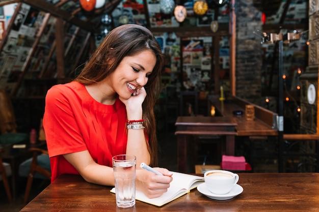 Caf inの机の上にコーヒーの一杯の日記の中に刻み目を書く幸せな女性