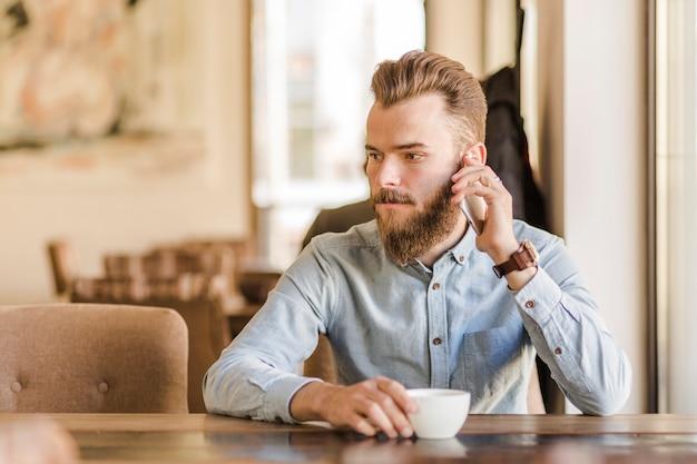 Caf inの携帯電話で話すコーヒーのカップを持つ若い男