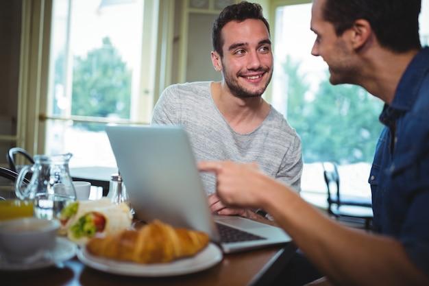 友達のテーブルに座って、cafa©にラップトップを使用して、