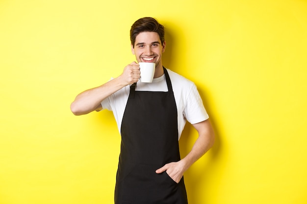 Cafe barista drinking cup of coffee and smiling, wearing black apron, standing over yellow background.