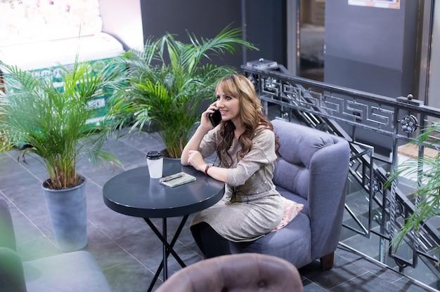 カフェシティライフスタイル女性のスマートフォンでコーヒーとテキストメッセージを飲む