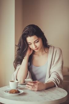 Женщина в кафе городского образа жизни на телефоне, отправка текстовых сообщений на приложение для смартфона, сидя в дверях