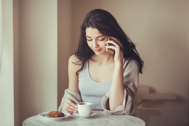 Женщина образа жизни города кафе разговаривает на смартфоне, сидя в дверях в модном городском кафе. крутой молодой