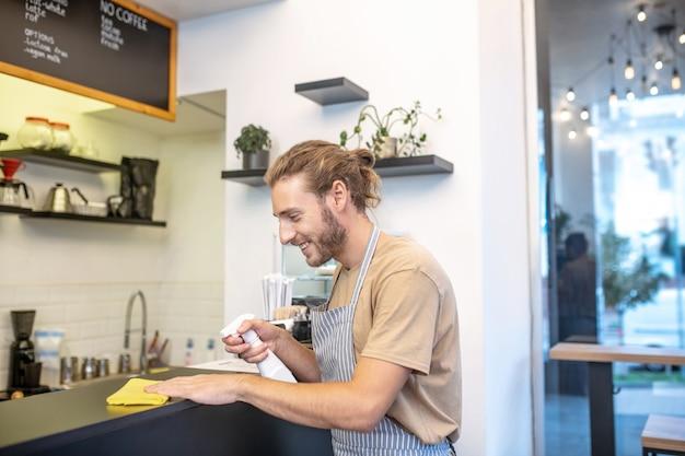 카페, 청소. 좋은 분위기에서 표면을 닦는 카페에서 청소 프로필에 긴 머리 젊은 수염 난된 남자