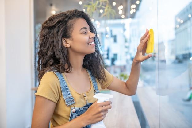 카페, 청소. 노란색 냅킨 카페에서 프로필 닦는 창에 긴 물결 모양의 머리를 가진 젊은 예쁜 여자