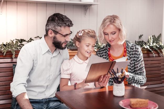 카페 고객. 그녀의 부모와 함께 앉아있는 동안 메뉴를 읽는 즐거운 긍정적 인 소녀